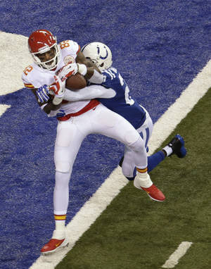 Photo - Kansas City Chiefs wide receiver Dwayne Bowe (82) scores a touchdown as Indianapolis Colts free safety Darius Butler (20) defends during the first half of an NFL wild-card playoff football game Saturday, Jan. 4, 2014, in Indianapolis. (AP Photo/AJ Mast)