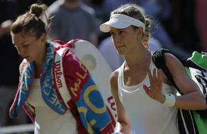 Photo - Eugenie Bouchard of Canada, right, waves as she walks off court with Simona Halep of Romania after she won their women's singles semifinal match at the All England Lawn Tennis Championships in Wimbledon, London, Thursday, July 3, 2014. Bouchard will play Petra Kvitova of Czech Republic in the final Saturday. (AP Photo/Pavel Golovkin)