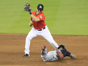 Photo - Atlanta Braves' Jordan Schafer, bottom, slides safely into second base with a steal in the ninth inning as Miami Marlins second baseman Ed Lucas tries to make the tag during a baseball game in Miami, Sunday, June 1, 2014. (AP Photo/Joe Skipper)