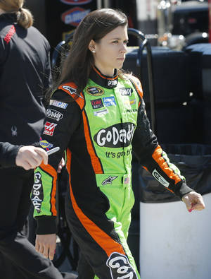 Photo - Driver Danica Patrick walks through the garage area before practice begin, Friday, May 9, 2014, at Kansas Speedway in Kansas City, Kan., for Saturday night's NASCAR Sprint Cup series auto race. (AP Photo/Orlin Wagner)