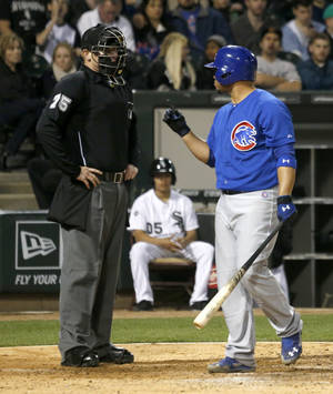 Photo - Chicago Cubs' Welington Castillo, right, has words with home plate umpire Tom Woodring, after Castillo was called out on strikes during the sixth inning of an interleague baseball game Wednesday, May 7, 2014, in Chicago. (AP Photo/Charles Rex Arbogast)