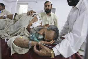 Photo -   A man who was injured in a suicide bombing in the tribal region of Khar in Bajur, is comforted by relatives, in a hospital in Peshawar, Pakistan, Friday, May 4, 2012. A suicide bombing in a Pakistani market close to the Afghan border killed 20 people Friday, officials said, a day after the U.S. released letters seized from Osama bin Laden's compound that criticized Pakistani militants for killing too many civilians. (AP Photo/Mohammad Sajjad)