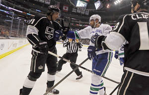 Photo - Vancouver Canucks center Ryan Kesler (17), right, and Los Angeles Kings center Jordan Nolan (71) square off in the second period of an NHL hockey game in Los Angeles Monday, Jan. 13, 2014.  (AP Photo/Reed Saxon)