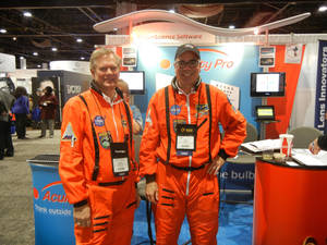 Photo - Jerry Carter, left,  and Dan Bintz, business partners in Acuity Pro vision-science software, pose wearing NASA jumpsuits at a recent optometry meeting trade show in Atlanta. PHOTO PROVIDED <strong></strong>