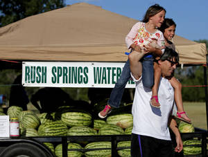 photo - Gary Anderson, of Oklahoma City, carries his 5-year-old daughters, Caroline, left, and Claire, on his shoulders before the 5k run.