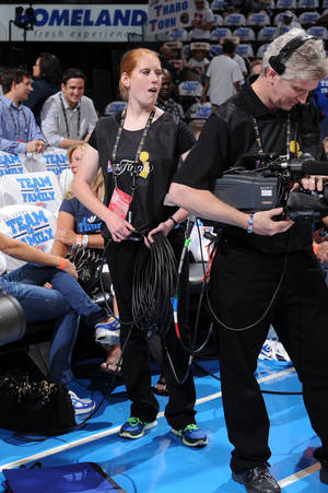photo - Army Reserve Spc. Elizabeth Fowler, of Oklahoma City, helps an NBA cameraman during a Finals game at the Chesapeake Energy Arena last week.  <strong>PHOTO BY ANDREW D. BERNSTEIN / NBAE </strong>