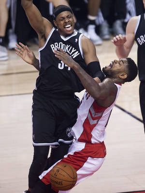 Photo - Toronto Raptors forward Amir Johnson, right, fouls Brooklyn Nets forward Paul Pierce, left, during the first half of Game 5 of the opening-round NBA basketball playoff series in Toronto, Wednesday, April 30, 2014. (AP Photo/The Canadian Press, Nathan Denette)