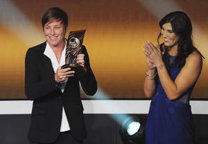 photo - Abby Wambach, left, of the United States is applauded by US goalkeeper Hope Solo, left, as she shows off the FIFA Women&#039;s World Player of the Year award during the FIFA Ballon d&#039;Or Gala 2013 held at the Kongresshaus in Zurich, Switzerland, Monday, Jan. 7, 2013. (AP Photo/Keystone, Steffen Schmidt)