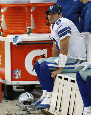 Photo - Dallas Cowboys quarterback Tony Romo seats on the beach as watches the action on the big screen television during the second half of an NFL football game against the Washington Redskins in Landover, Md., Sunday, Dec. 22, 2013. (AP Photo/Alex Brandon)