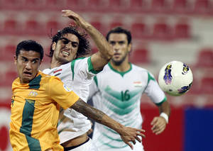photo -   Iraq's national team player Ahmed Ibrahim, right, challenges Tim Cahill, left, of Australia during the 2014 World Cup Asian qualifying football match in Doha, Tuesday, Oct. 16, 2012. (AP Photo/Osama Faisal)