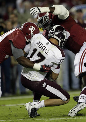 Photo -   Mississippi State quarterback Dak Prescott (15) is sacked by Alabama linebacker Denzel Devall (30) and defensive lineman Quinton Dial (90) during the first half of an NCAA college football game at Bryant-Denny Stadium in Tuscaloosa, Ala., Saturday, Oct. 27, 2012. (AP Photo/Dave Martin)