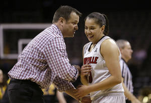 Photo - Louisville head coach Jeff Walz, left, laughs with guard Shoni Schimmel during the second half of an NCAA tournament second-round women's college basketball game against Iowa, Tuesday, March 25, 2014, in Iowa City, Iowa. (AP Photo/Charlie Neibergall)