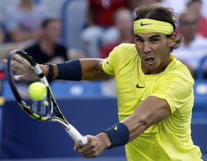 Photo - Rafael Nadal, from Spain, hits a backhand against Roger Federer, from Switzerland, during a quarterfinal match at the Western & Southern Open tennis tournament on Friday, Aug. 16, 2013, in Mason, Ohio. (AP Photo/Al Behrman)