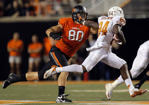 photo - Texas' Marquise Goodwin (84) tries to get by Oklahoma State's Cooper Bassett (80) during a college football game between Oklahoma State University (OSU) and the University of Texas (UT) at Boone Pickens Stadium in Stillwater, Okla., Saturday, Sept. 29, 2012. Texas on 41-36. Photo by Sarah Phipps, The Oklahoman