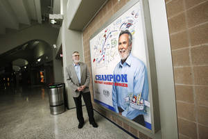 Photo - The Regional Food Bank of Oklahoma is one of six nonprofit agencies to be featured in Chesapeake Energy Corp.'s Cheering for Champions campaign. Executive Director Rodney Bivens stands near a sign bearing his picture Wednesday at Chesapeake Energy Arena. <strong>PAUL B. SOUTHERLAND - The Oklahoman</strong>