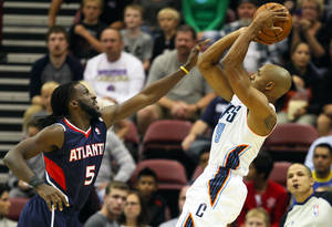 Photo - Charlotte Bobcats guard Gerald Henderson, right, takes a jump shot with Atlanta Hawks' DeMarre Carroll during the first half of a preseason NBA basketball game in Asheville, N.C., Tuesday, Oct. 8, 2013. (AP Photo/Adam Jennings)