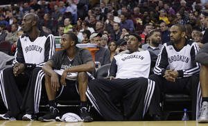 Photo - Brooklyn Nets' Kevin Garnett, Marquis Teague, Paul Pierce and Alan Anderson, from left, watch from the bench in the first quarter of an NBA basketball game against the Cleveland Cavaliers on Wednesday, April 16, 2014, in Cleveland. (AP Photo/Tony Dejak)