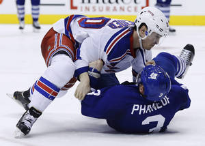 Photo - New York Rangers' Chris Kreider, left, takes Toronto Maple Leafs' Dion Phaneuf to the ice in a fight during the third period of an NHL hockey game in Toronto, Saturday, Jan. 4, 2014. (AP Photo/The Canadian Press, Mark Blinch)