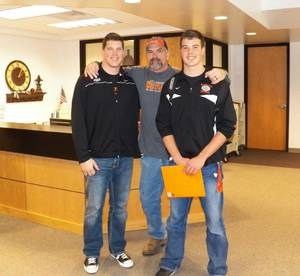 Photo - Cooper, left, and Dawson Bassett, right, with their father John. PHOTO PROVIDED
