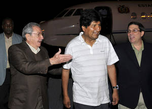 photo - In this picture released by the Cuban newspaper Juventud Revelde, Bolivia's President Evo Morales, center, is welcomed by Cuba's President Raul Castro, left, and Cuba's Foreign Minister Bruno Rodriguez at the Jose Marti international airport  in Havana, Cuba, early Sunday, Dec. 23, 2012. Evo Morales is in Cuba to visit Venezuela's President Hugo Chavez, who is recovering from a surgery, his fourth operation related to his pelvic cancer since June 2011. (AP Photo/Juventud Revelde, Estudios Revolucion)