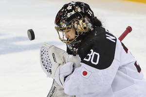 Photo - Goalkeeper Nana Fujimoto of Japan blocks a shot on goal during the second period of the 2014 Winter Olympics women's ice hockey game against Germany at Shayba Arena, Tuesday, Feb. 18, 2014, in Sochi, Russia. (AP Photo/Petr David Josek)