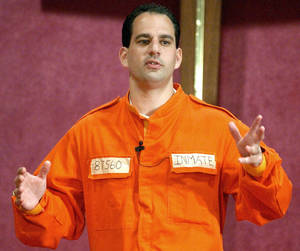 Photo - FILE - In this July 7, 2002 file photo, Barry Minkow, a convicted con artist and the co-founder of the for-profit Fraud Discovery Institute, wears a prison jumpsuit costume as he delivers a sermon on materialism at the Community Bible Church in San Diego. Minkow, who went from teenage millionaire to convicted con artist to professional fraud fighter and pastor, was convicted Wednesday, Jan. 22, 2014 of cheating his San Diego church congregation out of some $3 million. (AP Photo/Denis Poroy, File)
