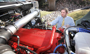 Photo - Peake Fuel Solutions has developed a dual-fuel system that allows heavy duty trucks to run on a mixture of diesel and compressed natural gas. Manager of Technology Services Bryan Curtis talks Nov. 9 about the natural gas injector on the top of the motor. Photo By David McDaniel, The Oklahoman