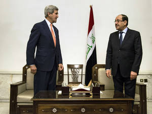 Photo - U.S. Secretary of State John Kerry, left, meets with Iraqi Prime Minister Nouri al-Maliki, right, at the Prime Minister's office in Baghdad on Monday, June 23, 2014. Kerry flew to Baghdad on Monday to meet with Iraq's leaders and personally urge the Shiite-led government to give more power to political opponents before a Sunni insurgency seizes more control across the country and sweeps away hopes for lasting peace. (AP Photo/Brendan Smialowski, Pool)