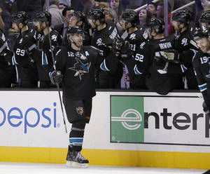 photo - San Jose Sharks center Patrick Marleau (12) high-fives teammates after scoring against the Vancouver Canucks during the second period of an NHL hockey game in San Jose, Calif., Sunday, Jan. 27, 2013. (AP Photo/Tony Avelar)