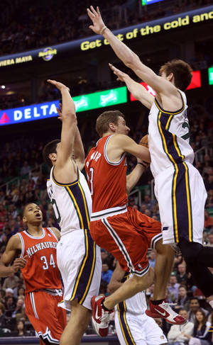 Photo - Milwaukee Bucks' Luke Ridnour, middle, attempts a shot as Utah Jazz's Enes Kanter, left, and Gordon Hayward, right, defend in the first half of an NBA basketball game Thursday, Jan. 2, 2014, in Salt Lake City. (AP Photo/Kim Raff)