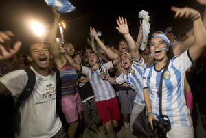 Photo - Soccer fans of the Argentina national soccer team celebrate their team's victory during a live broadcast of the soccer World Cup match between Argentina and the Netherlands, inside the FIFA Fan Fest area on Copacabana beach, in Rio de Janeiro, Brazil, Wednesday, July 9, 2014. Argentina made it to the World Cup final with a 4-2 shootout win over the Netherlands after the game finished in a 0-0 stalemate. (AP Photo/Silvia Izquierdo)