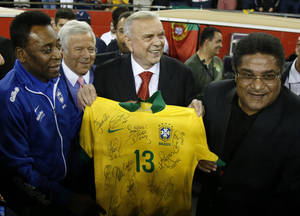 Photo - From left, Pele, New England Revolution owner Robert Kraft, Brazil Football Federation President Jose Maria Marin, and Eusebio pose with a Brazil soccer jersey prior to an international friendly soccer match between Portugal and Brazil, Tuesday, Sept. 10, 2013, in Foxborough, Mass. (AP Photo/Elise Amendola)