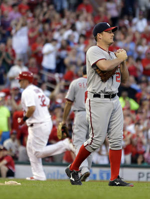 Photo - Washington Nationals starting pitcher Jordan Zimmermann, right, rubs up a new ball as St. Louis Cardinals' Matt Adams rounds the bases after hitting a solo home run during the second inning of a baseball game on Friday, June 13, 2014, in St. Louis. (AP Photo/Jeff Roberson)