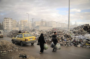 Photo -   In this Saturday, Nov. 10, 2012 photo, Syrians carry their rubbish to a mountain of garbage in a roundabout in Aleppo, Syria. Due the heavy fighting and shelling, the garbage collection system collapsed weeks ago. (AP Photo/Mónica G. Prieto)