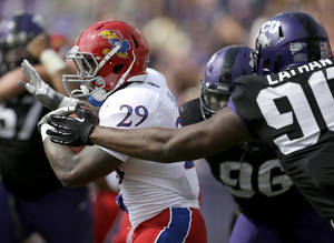 Photo - Kansas running back James Sims (29) breaks through the TCU defensive tackle Chucky Hunter (96) and Terrell Lathan (90) for extra yardage on a running play in the first half of an NCAA college football game, Saturday, Oct. 12, 2013, in Fort Worth, Texas. (AP Photo/Tony Gutierrez)