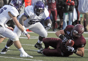 Photo - Montana defensive tackle Alex Bienemann, right,intercepts a pass in the fourth quarter against Weber State in an NCAA college football game in Missoula, Mont., Saturday, Nov. 16, 2013. (AP Photo/Michael Albans)