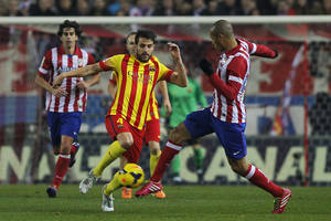 Photo - Barcelona's Cesc Fabregas, centre, in action with Atletico's Miranda, right,  during a Spanish La Liga soccer match between Atletico de Madrid and FC Barcelona at the Vicente Calderon stadium in Madrid, Spain, Saturday, Jan. 11, 2014. (AP Photo/Andres Kudacki)