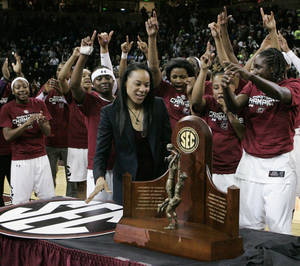 Photo - South Carolina coach Dawn Staley looks at the trophy after the team won the Southeastern Conference title with a 67-56 win over Georgia in an NCAA college basketball game Thursday, Feb. 27, 2014, in Columbia, S.C. (AP Photo/Mary Ann Chastain)