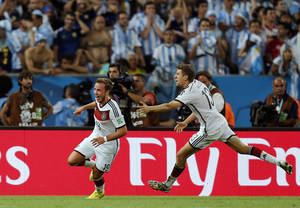 Photo - Germany's Mario Goetze, left, celebrates with Thomas Mueller after scoring the opening goal during the World Cup final soccer match between Germany and Argentina at the Maracana Stadium in Rio de Janeiro, Brazil, Sunday, July 13, 2014. Germany beat Argentina 1-0 to win its fourth World Cup title. (AP Photo/Frank Augstein)