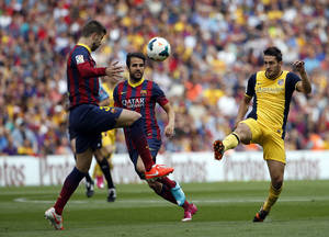 Photo - Barcelona's Gerard Pique, left, and Atletico's Koke, right, challenge for the ball during a Spanish La Liga soccer match between FC Barcelona and Atletico Madrid at the Camp Nou stadium in Barcelona, Spain, Saturday, May 17, 2014. (AP Photo/Emilio Morenatti)