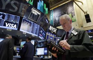 Photo - Trader James Riley works on the floor of the New York Stock Exchange Wednesday, Feb. 5, 2014. The U.S. stock market is edging lower in early trading after a modest recovery the day before. (AP Photo/Richard Drew)