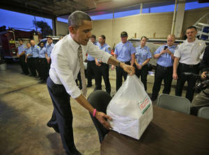Photo -   President Barack Obama delivers boxes of Krispy Kreme doughnuts, that he purchased nearby, to firefighters at Fire Station No. 14., during an unannounced visit, Thursday, Oct. 25, 2012, in Tampa, Fla. (AP Photo/Pablo Martinez Monsivais)