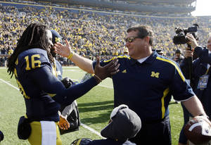 photo -   Michigan head coach Brady Hoke,right, greets quarterback Denard Robinson during a pre-game ceremony for seniors before an NCAA college football game against Iowa at Michigan Stadium in Ann Arbor, Mich., Saturday, Nov. 17, 2012. (AP Photo/Carlos Osorio)