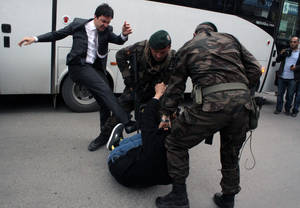 Photo - In this photo taken Wednesday, May 14, 2014  a person identified by Turkish media as Yusuf Yerkel, advisor to Turkish Prime Minister Recep Tayyip Erdogan, kicks a protester already held by special forces police members during Erdogan's visiting  Soma, Turkey. Erdogan was visiting the western Turkish mining town of Soma after Turkey's worst mining accident . AP Photo/Depo Photos) TURKEY OUT