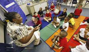 Photo - Above: Prekindergarten students listen to  Deborah Williams,  media specialist, tell a story at Greystone Lower Elementary School in Oklahoma City.