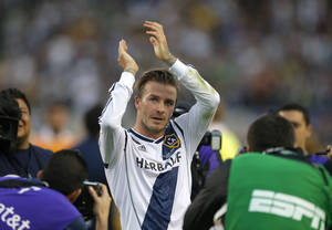 photo - FILE - In this Saturday, Dec. 1, 2012 file photo Los Angeles Galaxy's David Beckham, of England, acknowledges the fans as he leaves the field after the team's 3-1 win in the MLS Cup championship soccer match against the Houston Dynamo in Carson, Calif.  According to reports Thursday Jan. 31, 2013, David Beckham is to join Paris Saint-Germain.  (AP Photo/Jae C. Hong, File)