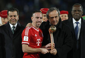 Photo - Best player of the tournament, Bayern's Franck Ribery, centre, stands on stage with UEFA president Michel Platini,  2nd right, and CAF President Issa Hayatou, right,  after receiving his award after the final of the soccer Club World Cup  between FC Bayern Munich and Raja Casablanca in Marrakech, Morocco, Saturday, Dec. 21, 2013. (AP Photo/Christophe Ena)