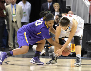 Photo - LSU's Jasmine Rhodes, left, battles Louisville's Shoni Schimmel for a loose ball during the first half in a regional semifinal game at the NCAA women's college basketball tournament on Sunday, March 30, 2014, in Louisville, Ky. (AP Photo/Timothy D. Easley)