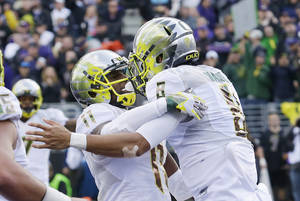 Photo - Oregon quarterback Marcus Mariota, right, celebrates with wide receiver Bralon Addison after Mariota scored a touchdown against Washington in the second half of an NCAA college football game, Saturday, Oct. 12, 2013, in Seattle. Oregon won 45-24. (AP Photo/Ted S. Warren)