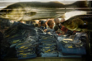 "Photo -   Shoppers pick through stacks of discounted jeans beside a giant aquarium inside Bass Pro Shops after the doors opened at 5 a.m., kicking off ""Black Friday"" and the holiday shopping season in Memphis, Tenn. Friday Nov. 23, 2112.. Some bargain-hunters waited outside the store for four and a half hours in the rain for the chance to be first in line. For the first time many retailers opened as early as 8 p.m. on Thursday sparking some criticism for shortening their employees' Thanksgiving holiday. (AP Photo, Brandon Dill, Commercial Appeal)"